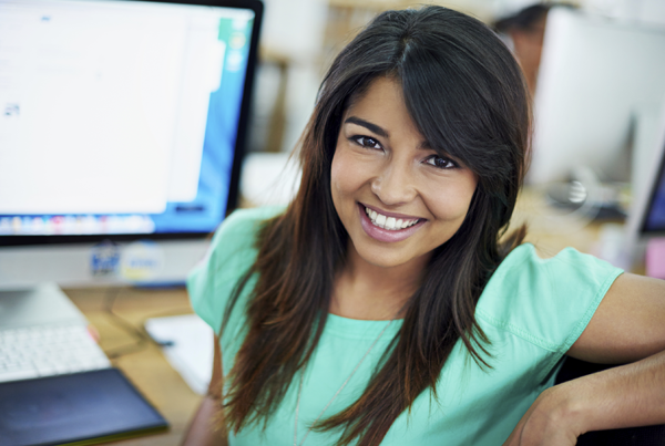 Smiling young woman at her computer